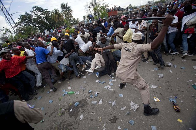 A police officer uses his baton to beat back supporters of Haiti's former President Jean-Bertrand Aristide who gathered outside the courthouse where Aristide arrived earlier in the day, in Port-au-Prince, on May 8, 2013. The two-time president showed up at the courthouse to testify before a judge investigating the 2000 slaying of Jean Dominique, one of the Caribbean country's most prominent journalists. (Photo by Dieu Nalio Chery/Associated Press)