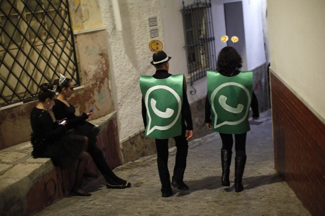 Revellers dressed up as dancers of 'Black Swan' check their mobile phones next to revellers dressed up as a Whatsapp logo as they take part in New Year's celebrations in Coin, near Malaga, southern Spain, early January 1, 2015. (Photo by Jon Nazca/Reuters)