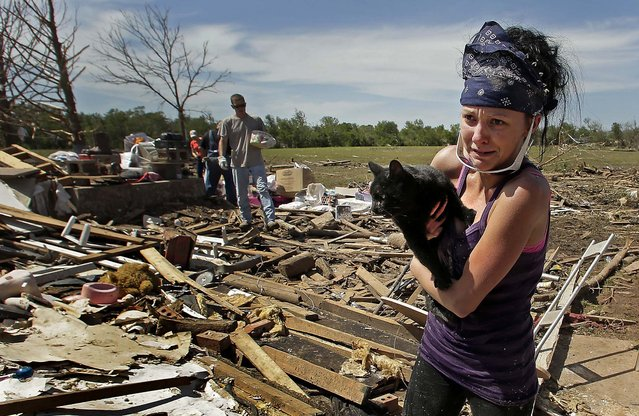"Brittany Brown rushes to get aid after finding her grandmother's cat ""Kitty"" which was buried in tornado rubble for two days. (Photo by Charlie Riedel/Associated Press)"