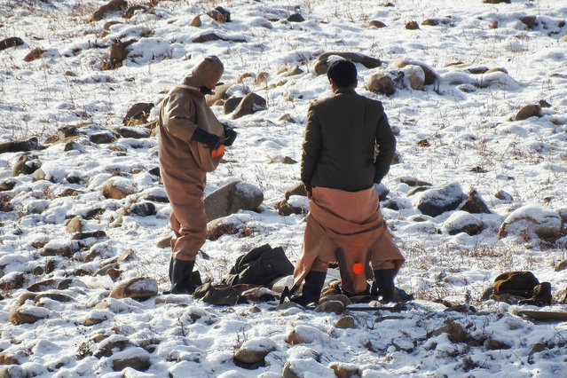 North Koreans are photographed from the Chinese side of the border as they stand next to the freezing Yalu River near the town of Linjiang, China, November 22, 2017. On a road trip along China's side of its border with North Korea, reporters found a group of North Koreans diving in the Yalu river who the Chinese locals said were searching for gold. (Photo by Damir Sagolj/Reuters)