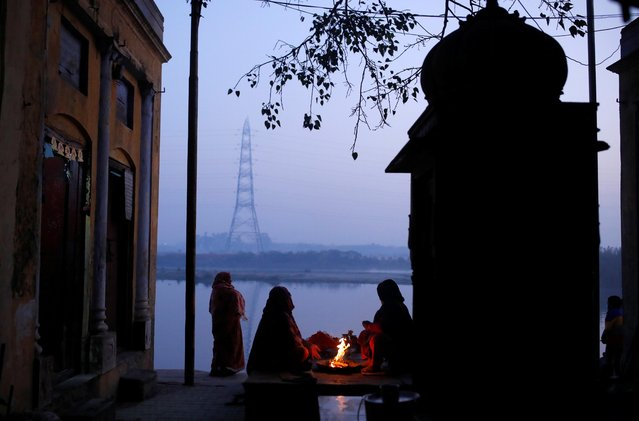 Women sit next to a bonfire on the banks of the Yamuna river on a winter morning in New Delhi, India, December 29, 2020. (Photo by Adnan Abidi/Reuters)