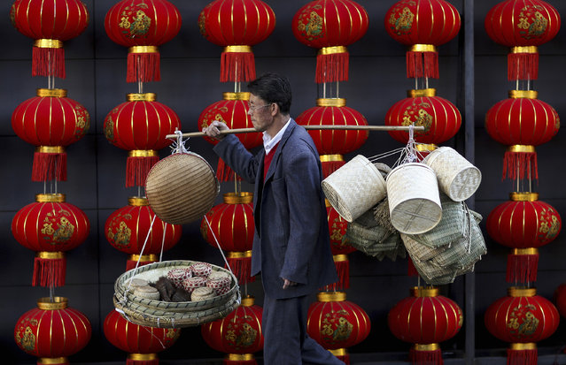 A basket vendor walks past red lanterns serving as decorations to celebrate the new year outside a shopping mall in Kunming, Yunnan province January 6, 2015. China's services sector grew at its fastest pace in three months in December as new orders remained strong, a private survey showed, an encouraging sign of strength even as manufacturing activity slows and the property market softens. (Photo by Reuters)