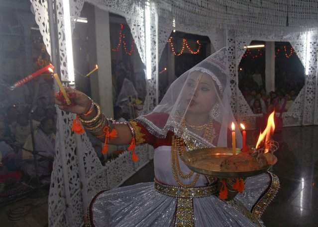 An artist wearing a traditional dress lights a candle as she performs during the Hindu festival of Maha Raas in Agartala, India, November 26, 2015. (Photo by Jayanta Dey/Reuters)