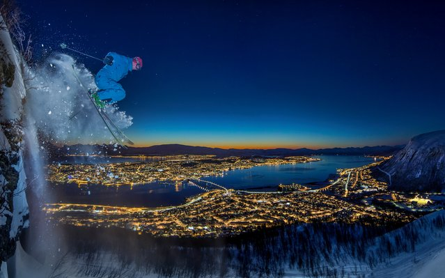 """""""Urban skiing in the Arctic"""". The photographer's friend descends a 10-metre high clifftop in Tromsø, Norway. It was challenging because the night was much darker than it appears in the photo and it was impossible to see where one might land. The image is the result of a long exposure and using a flash to capture the subject during action. Winner: Sport. (Photo by Audun Rikardsen/SIPA Contest)"""
