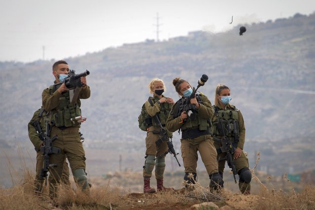 Israeli soldiers fire tear gas towards Palestinian demonstrators during a protest against the expansion of Israeli settlements near the West Bank village of Aqraba, north of Nablus, Wednesday, January 13, 2021. (Photo by Majdi Mohammed/AP Photo)