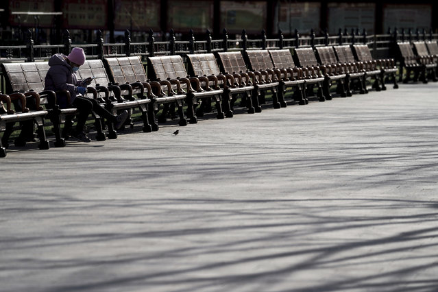 A woman wearing a face mask to help curb the spread of the coronavirus takes a rest on the bench at the Forbidden City in Beijing, Sunday, January 10, 2021. More than 360 people have tested positive in a growing COVID-19 outbreak south of Beijing in neighboring Hebei province. (Photo by Andy Wong/AP Photo)