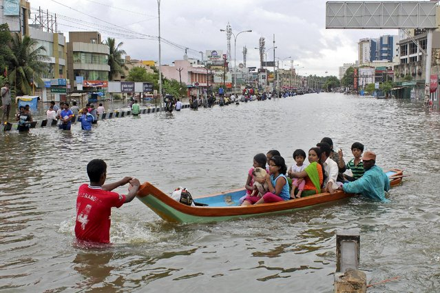 People travel on a boat as they move to safer places through a flooded road in Chennai, India, December 2, 2015. (Photo by Reuters/Stringer)