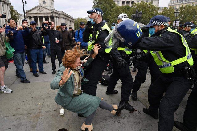 "A woman falls as police move in to disperse protesters in Trafalgar Square in London on September 26, 2020, at a ""We Do Not Consent!"" mass rally against vaccination and government restrictions designed to fight the spread of the novel coronavirus, including the wearing of masks and taking tests for the virus. (Photo by Justin Tallis/AFP Photo)"
