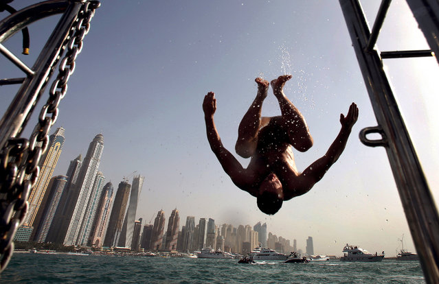 In this April 24, 2015 photo, a man does a flip into the water opposite the Marina Waterfront skyline in Dubai, United Arab Emirates. (Photo by Kamran Jebreili/AP Photo)