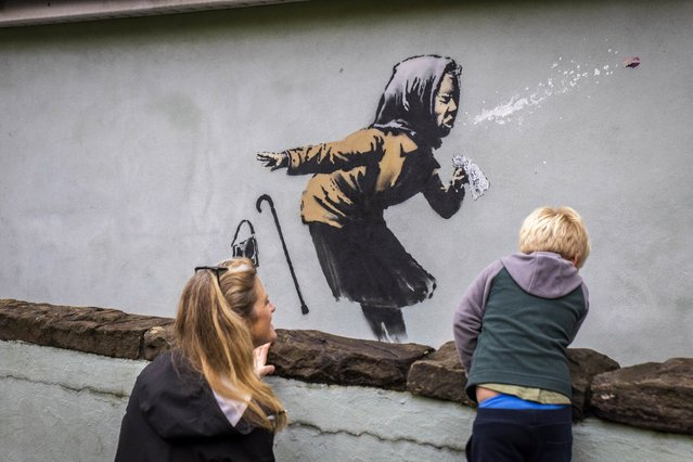 A potential Banksy has appeared on Vale Street in Bristol, United Kingdom on December 10, 2020. The elusive artist is from the city and is known for creating new works without anyone catching him in the act. An image of an old woman sneezing without covering her mouth has been spotted on a wall in the Totterdown area - a possible nod to the current health crisis. Crowds are already gathering at the bottom of Vale Street – one of Britain's steepest roads – to take pictures and discuss. (Photo by South West News Service/Action Press)