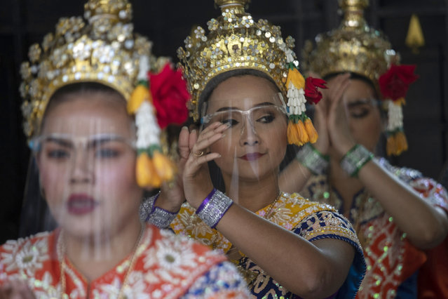Thai classical dancers wearing face shields to help curb the spread of the coronavirus perform at the Erawan Shrine in Bangkok, Thailand, Tuesday, January 12, 2021. Thailand's government announced new measures, including partial lockdowns with strict travel restrictions in some areas. Schools, bars, gambling parlors and other public gathering places have been closed. (Photo by Sakchai Lalit/AP Photo)