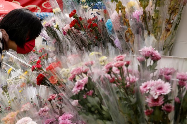 A customer, wearing a face mask, smells flowers during a Lunar New Year fair at Victoria Park in Hong Kong, China on February 11, 2021. (Photo by Tyrone Siu/Reuters)
