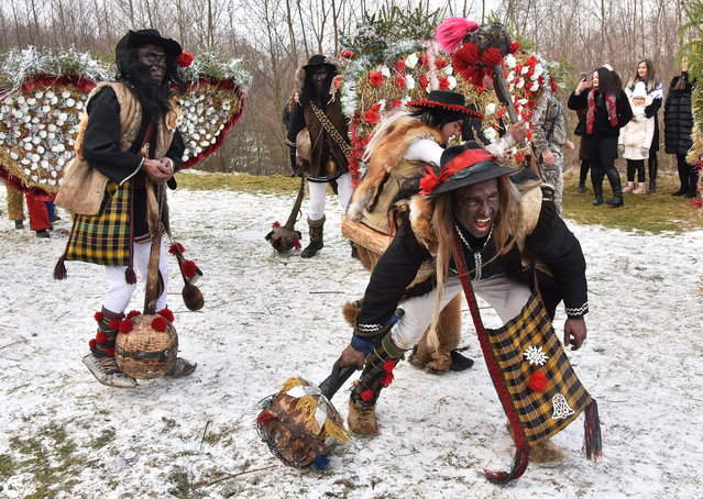 Local residents dressed in costumes perform during celebrations for Malanka traditional holiday, which is celebrated on the day of St. Basil and St. Melania, in the settlement of Krasnoilsk in Chernivtsi Region, Ukraine January 14, 2021. During the celebrations youngsters and adults wear traditional, carnival costumes, masks and visit local houses while singing carols, playing pranks or performing short plays. (Photo by Pavlo Palamarchuk/Reuters)