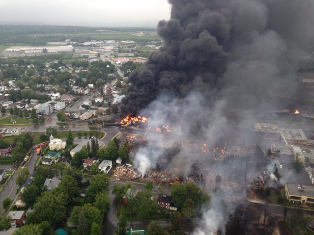 This aerial photo shows a fire in the town of Lac-Megantic as seen from a Sûreté du Québec helicopter Saturday, July 6, 2013 following a train derailment that sparked several explosions in Lac Megantic, Quebec. (Photo by AP Photo/The Canadian Press)