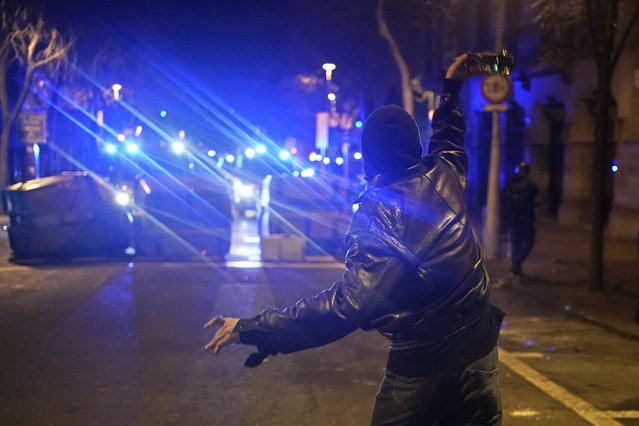 A demonstrator throws a bottle towards police vans during a protest condemning the arrest of rap singer Pablo Hasél in Barcelona, Spain, Saturday, February 20, 2021. A fifth night of peaceful protests to denounce the imprisonment of a Spanish rap artist once more devolved into clashes between police and fringe group members who set up street barricades and smashed storefront windows in Barcelona. (Photo by Joan Mateu/AP Photo)