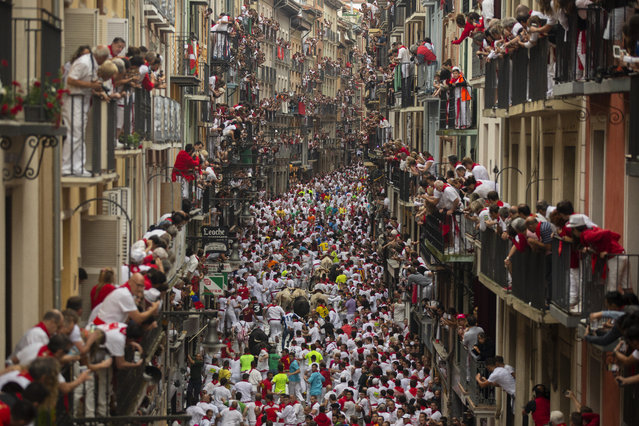"Revellers run with Puerto de San Lorenzo's fighting bulls during the second day of the San Fermin Running of the Bulls festival on July 7, 2018 in Pamplona, Spain. The annual Fiesta de San Fermin, made famous by the 1926 novel of US writer Ernest Hemmingway entitled ""The Sun Also Rises"", involves the daily running of the bulls through the historic heart of Pamplona to the bull ring. (Photo by Pablo Blazquez Dominguez/Getty Images)"