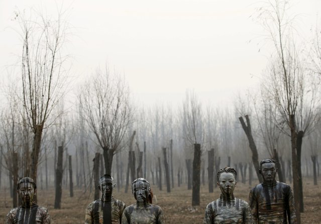 """Models painted in camouflage colours to blend in with the background pose for Chinese artist Liu Bolin's artwork """"""""Dongji"""", or Winter Solstice, on the second day after China's capital Beijing issued its second ever """"red alert"""" for air pollution, in Beijing, China, December 20, 2015. (Photo by Kim Kyung-Hoon/Reuters)"""