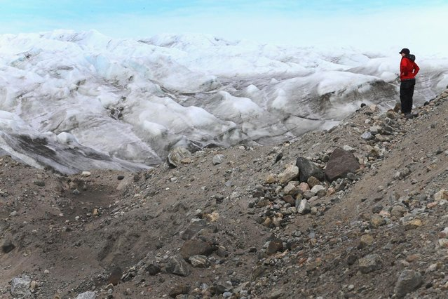 Kelly Deuerling, a Ph.D. candidate and NSF Graduate Research Fellow at the University of Florida, looks out onto a glacier as she takes part in a study to analyze the water chemistry coming out of the glacial environment and using that to understand how the melt is effecting the sea waters on July 10, 2013 in Kangerlussuaq, Greenland. (Photo by Joe Raedle/Getty Images via The Atlantic)