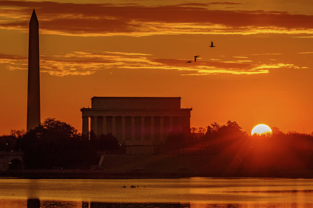 The sun peaks over the horizon next to the Washington Monument and Lincoln Memorial at daybreak along the Potomac River in Washington, Tuesday, March 6, 2018. (Photo by J. David Ake/AP Photo)