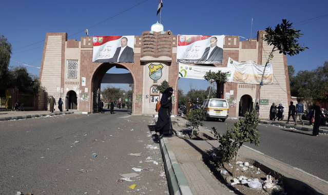 Yemenis pass the main gate of Sana'a University, with banners depicting the portraits of slain top Houthi leader saleh ali al-sammad, where a two-year-long 2011-uprising protest camp was set up, ahead of the tenth anniversary of the uprising, in Sana'a, Yemen, 20 January 2021. Yemen on 27 January 2021 marks the 10th anniversary of the 2011 Arab Spring uprising that toppled the then-president Ali Abdullah Saleh. (Photo by Yahya Arhab/EPA/EFE)