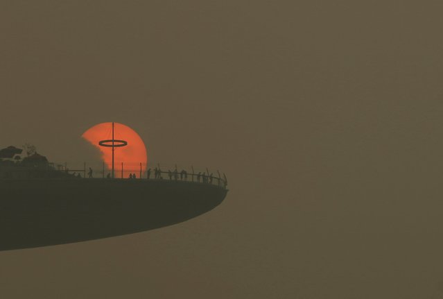 People watch the sun set from the observatory deck of the Marina Bay Sands hotel in Singapore October 5, 2015. Slash-and-burn agriculture in neighboring Indonesia blanketed Singapore in a choking haze. (Photo by Edgar Su/Reuters)