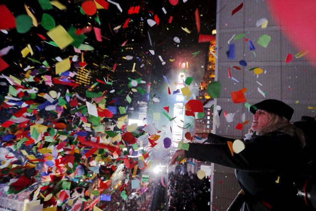 Revelers throw confetti from a balcony to celebrate during New Year festivities above Times Square in New York January 1, 2016. (Photo by Lucas Jackson/Reuters)