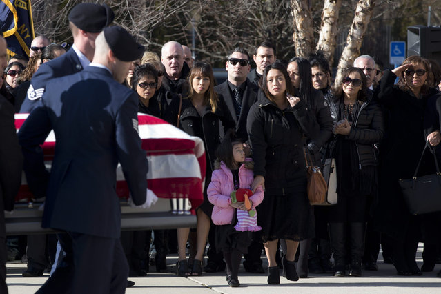 Staff Sgt. Louis Bonacasa's wife, Deborah, center, and 5-year-old daughter, Lilianna, watch as a military honor guard carries his casket into the New Beginnings Christian Center for his funeral service, Saturday, January 2, 2016, in Coram, N.Y. Bonacasa was one of six Americans killed last week in a suicide bombing in Afghanistan. (Photo by Mary Altaffer/AP Photo)