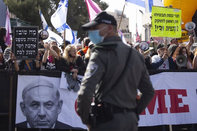 A police officer stands guard in front of protesters as Prime Minister Benjamin Netanyahu's motorcade arrives at the District Court in Jerusalem for a hearing in his corruption trial, Monday, April 5, 2021. Netanyahu was back in court for his corruption trial on Monday as the country's political parties were set to weigh in on whether he should form the next government after a closely divided election or step down to focus on his legal woes. (Photo by Maya Alleruzzo/AP Photo)