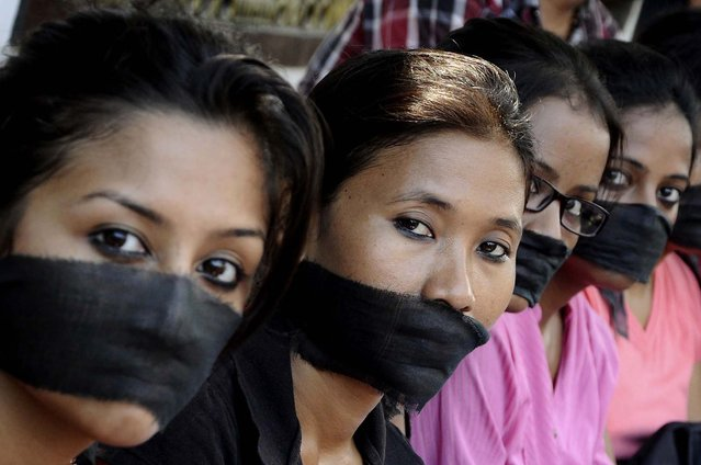 Members of the All Assam Photojournalist Association wear black sashes around their mouths during a protest against the rape of a photojournalist by five men inside an abandoned textile mill in Mumbai, in the northeastern Indian city of Guwahati, on August 24, 2013. The gang-rape of the 22-year-old journalist has drawn comparisons to an attack in December that led to nationwide protests and a revision of rape laws. (Photo by Utpal Baruah/Reuters)