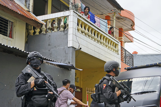 Residents look on as police officers stand guard during a raid on a house that, police believe, is linked to the suicide bombers of Sunday's church attack, in Makassar, South Sulawesi, Indonesia, Monday, March 29, 2021. Two attackers believed to be members of a militant network that pledged allegiance to the Islamic State group blew themselves up outside the packed Roman Catholic cathedral during a Palm Sunday Mass on Indonesia's Sulawesi island, wounding a number of people, police said. (Photo by Daeng Mansur/AP Photo)