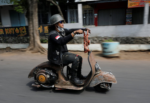 An extreme Vespa enthusiast rides his bike after attending weekend festival for extreme Vespas in Semarang, Central Java, Indonesia, July 22, 2018. (Photo by Darren Whiteside/Reuters)