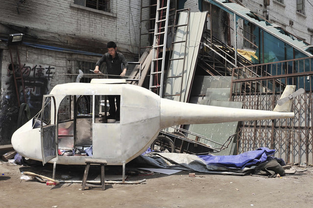 Gao Hanjie installs the rotor blades on his homemade helicopter in Shenyang, Liaoning province June 9, 2010. The graphic designer and helicopter enthusiast, with help from his friends, has spent more than a month building the 6-meter-long and 350kg helicopter. Gao claims he will eventually fly the contraption as a personal project according to local media. (Photo by Sheng Li/Reuters)