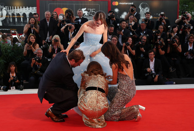 "(From L) Director Brady Corbet, actress Natalie Portman and actress Stacy Martin assist actress Raffey Cassidy (C) with her dress as they arrive for the premiere of the film ""Vox Lux"" presented in competition on September 4, 2018 during the 75 th Venice Film Festival at Venice Lido. (Photo by Tony Gentile/Reuters)"