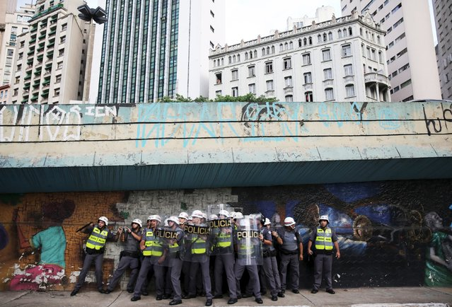 Riot police protect themselves behind shields as object are thrown at them by demonstrators during a protest against fare hikes for city buses in Sao Paulo, Brazil, January 8, 2016. (Photo by Nacho Doce/Reuters)