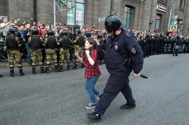 A Russian police officer detains a teenager during rally protesting retirement age hikes in St. Petersburg, Russia, Sunday, September 9, 2018. A government plan to increase the age for collecting state pensions brought protests across Russia's 11 time zones on Sunday even though the opposition leader who called them was in jail. Nearly 300 people were reported arrested. (Photo by Roman Pimenov/Interpress photo via AP Photo)