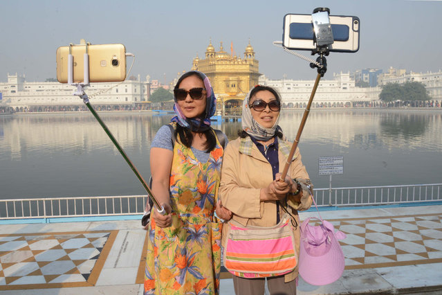 "Chinese tourists take a ""selfie"" at the Golden Temple in Amritsar on November 14, 2016, as Sikh devotees mark the 547 th birth anniversary of Sri Guru Nanak Dev. Guru Nanak was the founder of the Sikh religion and the first of ten Sikh gurus. (Photo by Narinder Nanu/AFP Photo)"