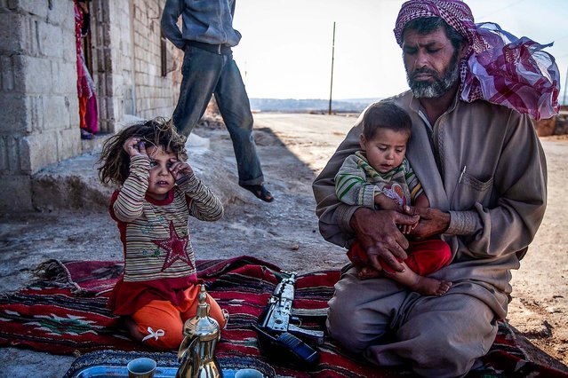 """A """"Free Syrian Army"""" fighter holds his son outside their home in Habit village, the Syrian central province of Hama, on September 25, 2013. (Photo by Associated Press)"""