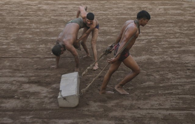 A Pakistani Kushti wrestler prepares the grpund in the ring while others practice during a training session, in Lahore, Pakistan, Tuesday, January 5, 2016. (Photo by K.M. Chaudary/AP Photo)