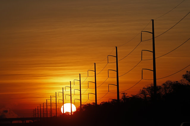In this January 31, 2018, file photo, the sun rises beyond power lines in St. Charles Parish, La. Homeland Security officials say that Russian hackers used conventional tools to trick victims into entering passwords in order to build out a sophisticated effort to gain access to control rooms of utilities in the U.S. The victims included hundreds of vendors that had links to nuclear plants and the electrical grid. (Photo by Gerald Herbert/AP Photo)