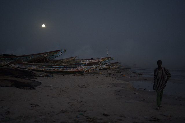 A man walks past pirogues used as fishing boats as the full moon rises over Bargny, Senegal, some 35 kilometers (22 miles) east of Dakar, Senegal, Monday April 26, 2021. The first true fishing season since the pandemic devastated the industry kicked off, bringing renewed hope to the fish processors, their families and the village, even as challenges from coronavirus and more remain. (Photo by Leo Correa/AP Photo)