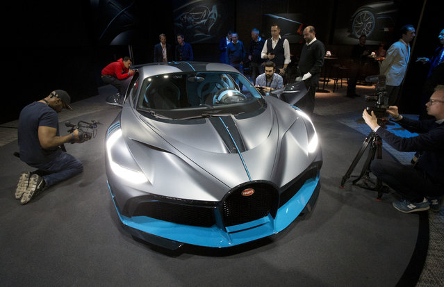 Media people gather next to a 5 million euro (5.8 $) Bugatti Divo during a media presentation on the eve of Paris Auto Show in Paris, Monday, October 1, 2018. (Photo by Michel Euler/AP Photo)