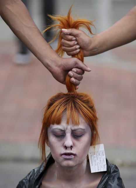 A young woman takes part in a street play depicting police brutality during an anti-government protest, in Bogota, Colombia, Saturday, May 15, 2021. Thousands of young people and college students have been at the forefront of Colombia's anti-government protests for more than two weeks. (Photo by Fernando Vergara/AP Photo)