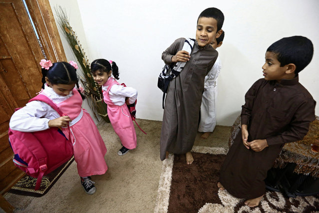 Saudi children of al-Fefi family prepare themselves before they go to their school through Fifa Mountain, in Jazan, south of Saudi Arabia, December 15, 2016. (Photo by Mohamed Al Hwaity/Reuters)