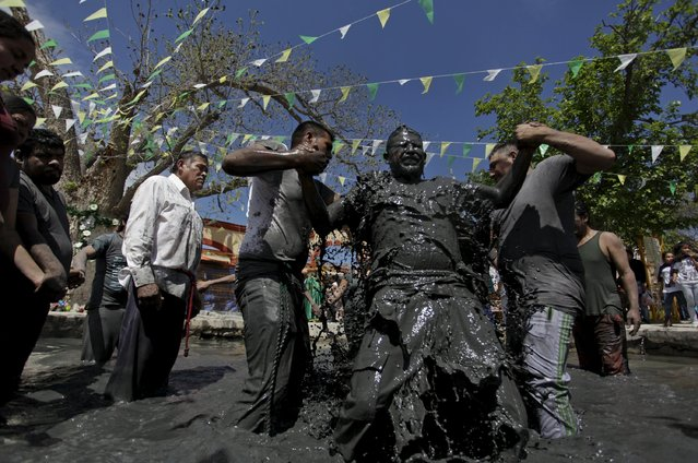 A penitent is baptised in a puddle of mud during celebrations for El Nino Fidencio in the town of Espinazo, on the outskirts of Monterrey March 19, 2015. Thousands of pilgrims from across the Americas descend on the town between March and October to visit the tomb of El Nino Fidencio, an eerie man-child figure famed for his playful cures and folk wisdom dispensed in a shrill contralto during the 1920s and 1930s. (Photo by Daniel Becerril/Reuters)