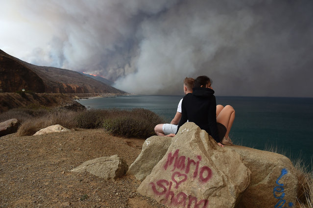 A couple looks out toward the Woolsey Fire as it blows toward the ocean along Pacific Coast Highway (Highway 1) near Malibu, California, November 9, 2018. About 75,000 homes have been evacuated in Los Angeles and Ventura counties due to two fires in the region. (Photo by Robyn Beck/AFP Photo)
