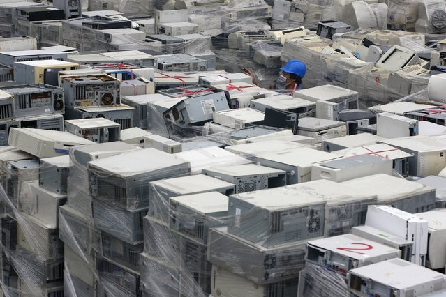 A man walks among piles of discarded computers at one of Taiwan's largest recycling factories in Taoyuan county, northern Taiwan in this November 24, 2009 file photo. Taiwan is expected to report manufacturing PMI numbers this week. (Photo by Pichi Chuang/Reuters)
