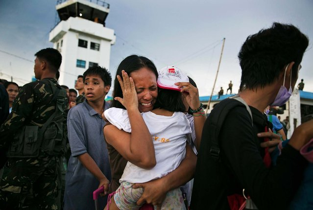 A woman carrying a child cries as other survivors of Typhoon Haiyan wait to board a C130 aircraft during the evacuation of hundreds of survivors in Tacloban on Tuesday. (Photo by Paula Bronstein/Getty Images)