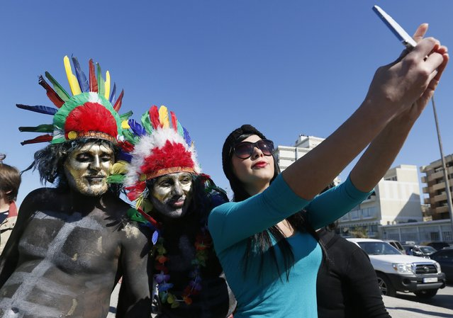 A woman takes selfie with participants of parade, held as part of the annual Zambo carnival, in the coastal city of Tripoli, northern Lebanon February 22, 2015. (Photo by Jamal Saidi/Reuters)