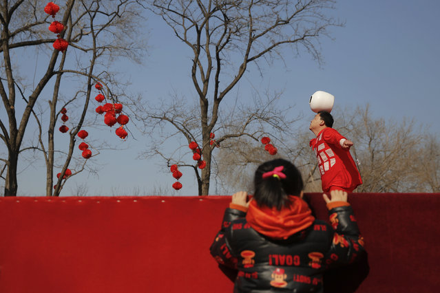 A girl watches an acrobatic performance at the Longtan park as the Chinese Lunar New Year, which welcomes the Year of the Monkey, is celebrated in Beijing, China February 9, 2016. (Photo by Damir Sagolj/Reuters)