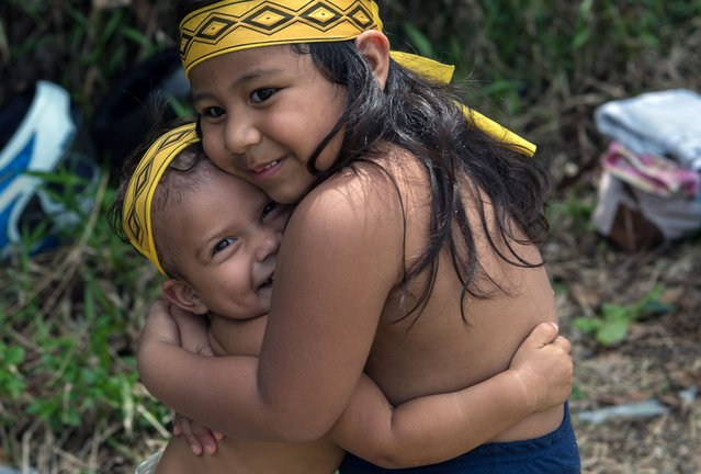 Indigenous children hug during the final match of Peladao, the amateur football tournament, in Manaus, Amazonas state, Brazil, on November 24, 2013. (Photo by Yasuyoshi Chiba/AFP Photo)